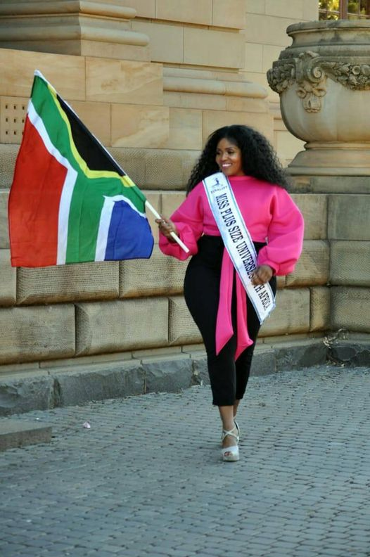 Black women in pink shirt and beauty pageant sash holding a South African flag in front of a brown building