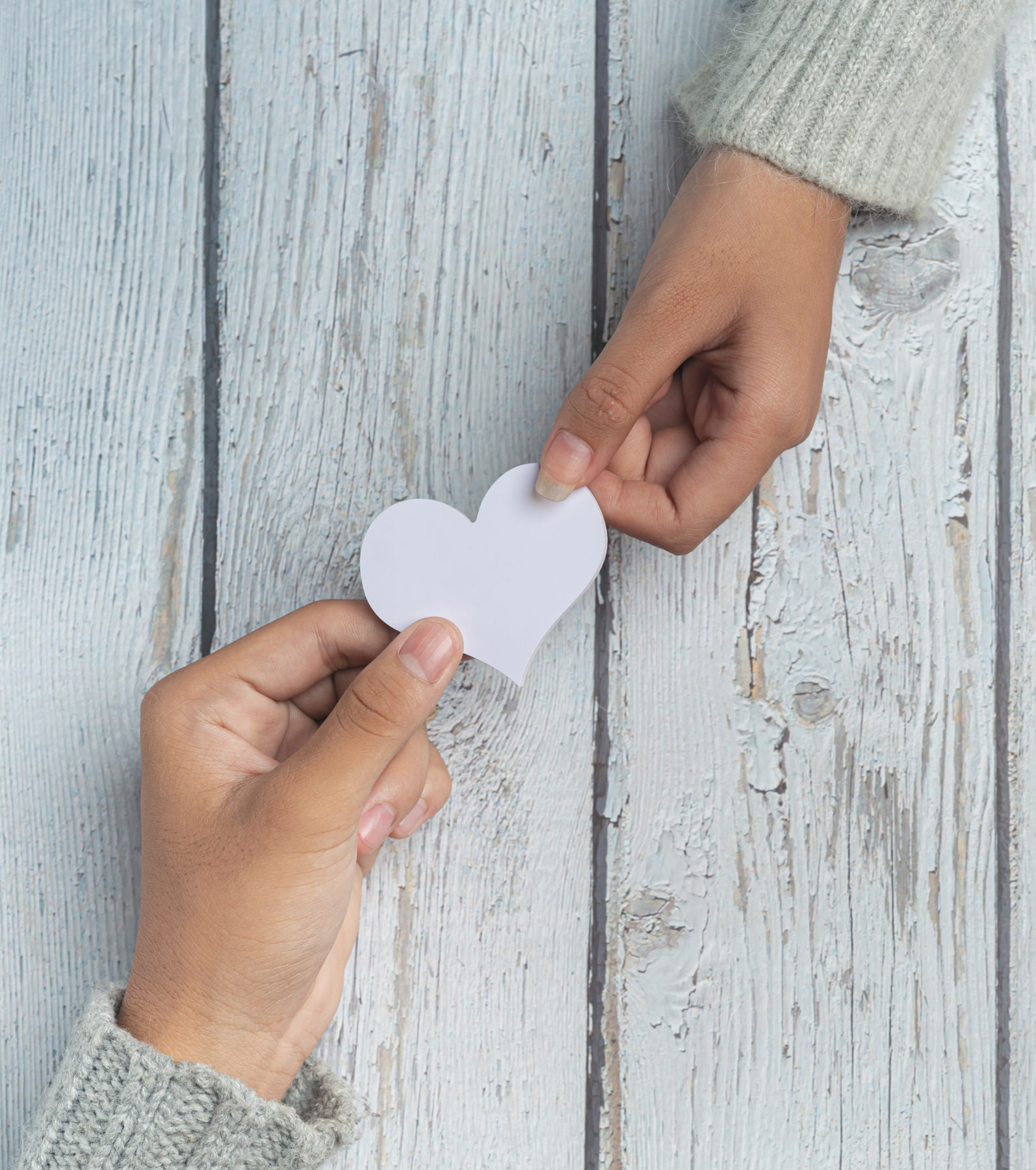 Two people holding a paper heart between their hands over a table