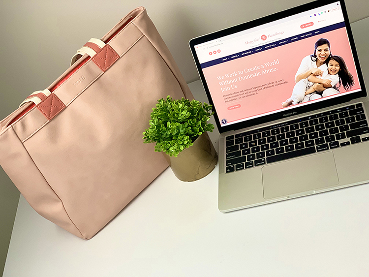 Coral handbag on white desk with small pant and laptop showing Hopefull Handbags webpage
