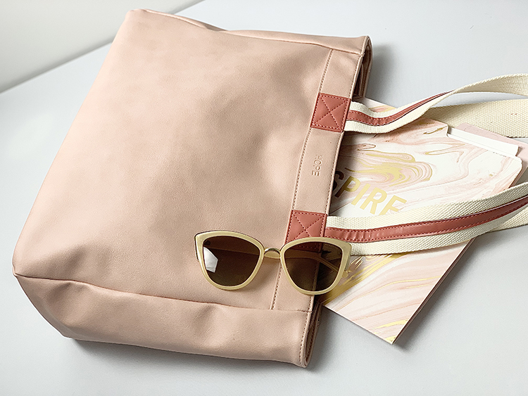 close up of coral bag with darker coral and white stripe straps on white desk with journal and sunglasses