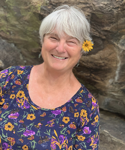 women with short gray hair, yellow flower above left ear, shirt with dark blue background and flower print