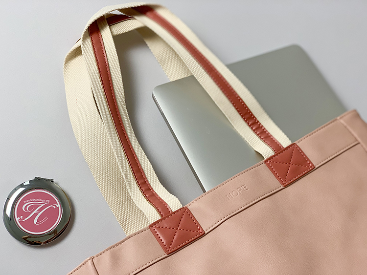 Close up of coral bag with white and darker coral striped straps and HH logo