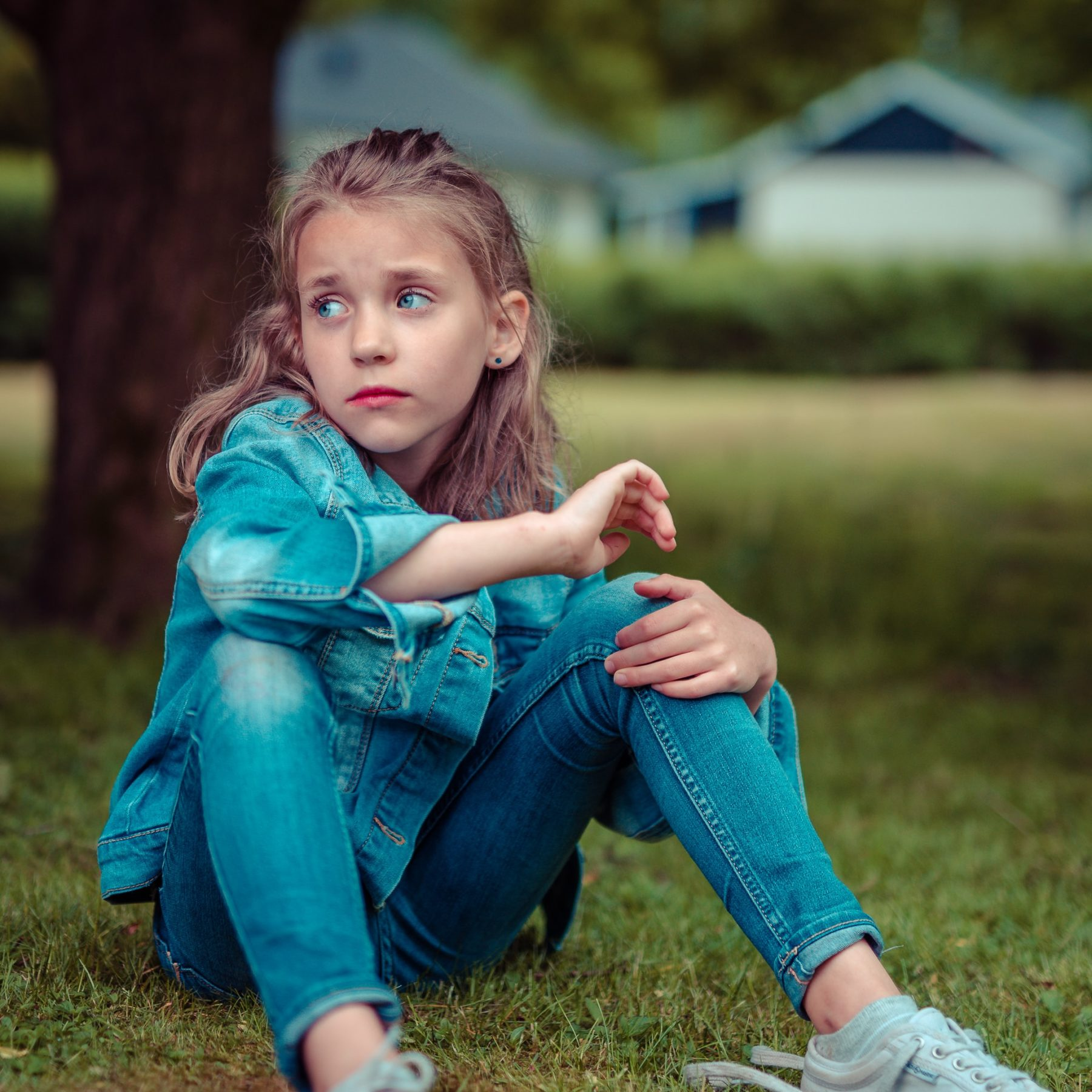 Scared, sad child sitting on grass in blue jeans and jean jacket