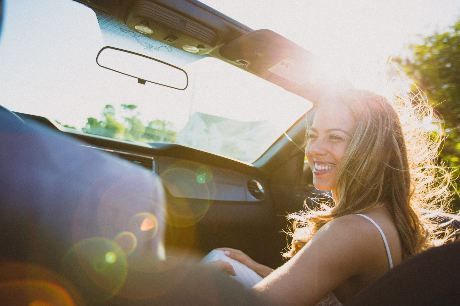 young women smiling while riding in a convertible with top down