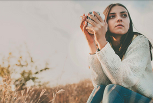 woman with long brown hair sitting in a field in sweater and jeans clasping a mug